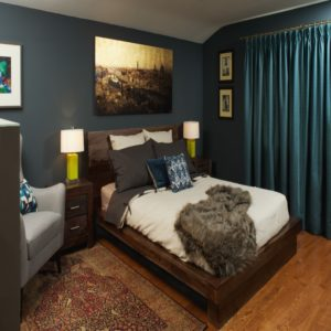 wide shot of dark blue bedroom with wood furniture and blue draperies