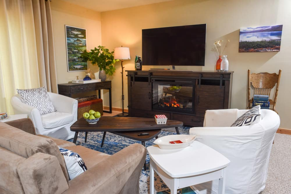 wide shot of cottage basement makeover with sofa, tub chairs and fireplace console