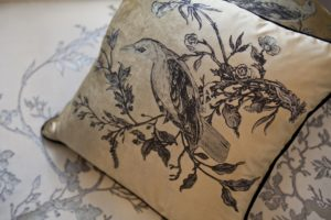 tight shot of timorous beasties textle on decor cushion on wallpaper design