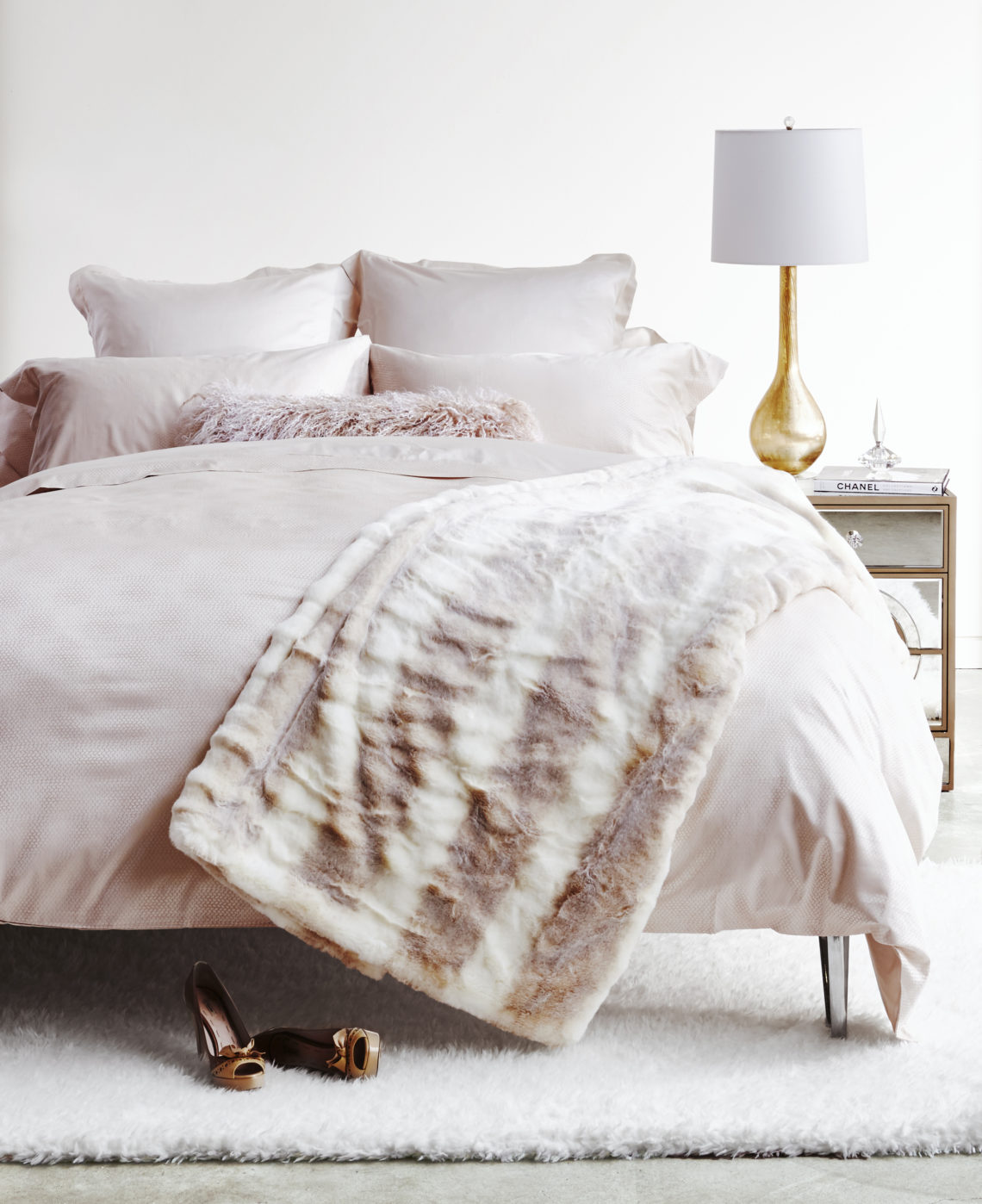 wide shot of faux fur throw on creamy white bedroom