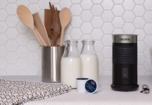 keurig milk frother with retro milk bottles and wooden spoons on kitchen counter