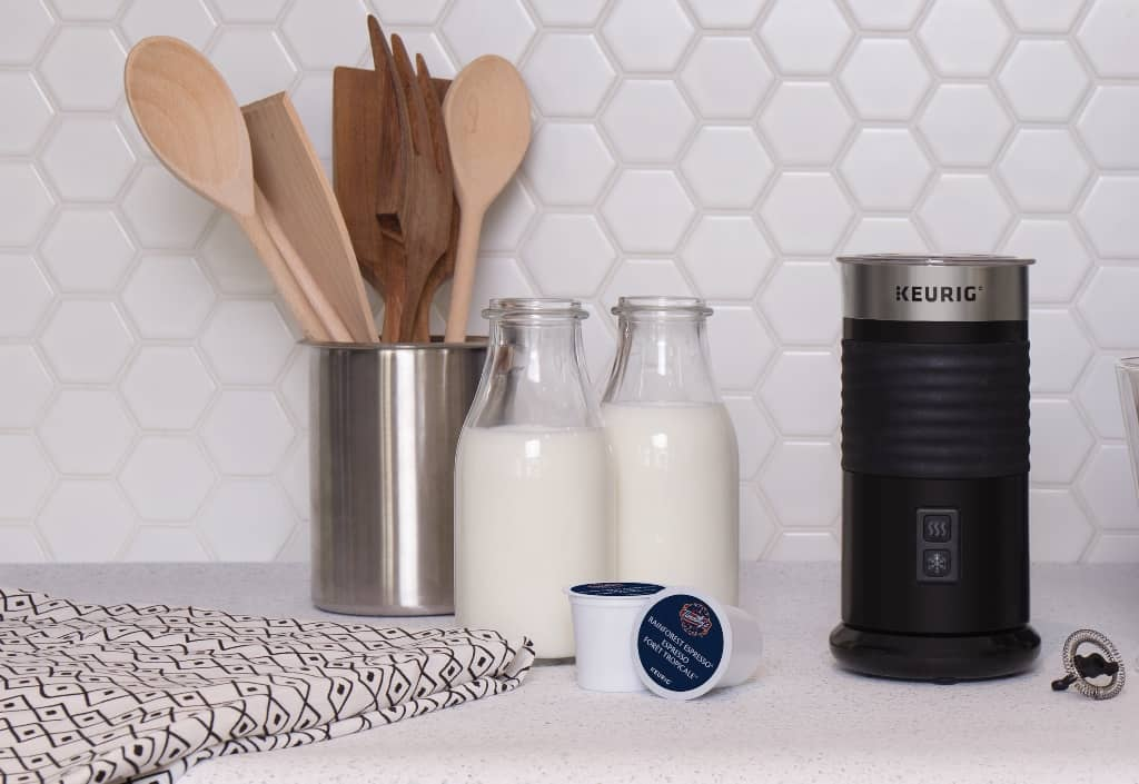 Keurig Milk frother on a countertop with bottles of cold milk and kitchen tools against a hexangal white tile backsplash.