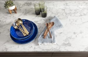 laminiate countertop in real-looking stone design with blue plates and gold flatware