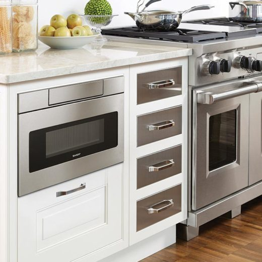 tight shot of Sharp Microwave drawer with black marble counter in white ktichen