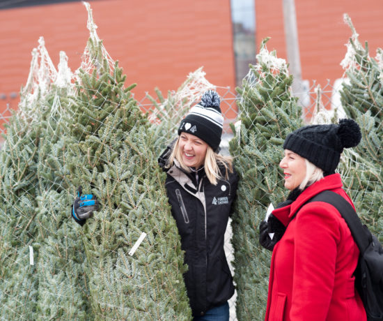 two women butying a real christmas tree from local sellers