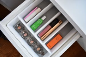 tight shot of an open drawer from a dressing table with a cultlery tray to organize toiletries.