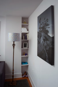 DIY shelves tucked into a small room to provide space ina guest room