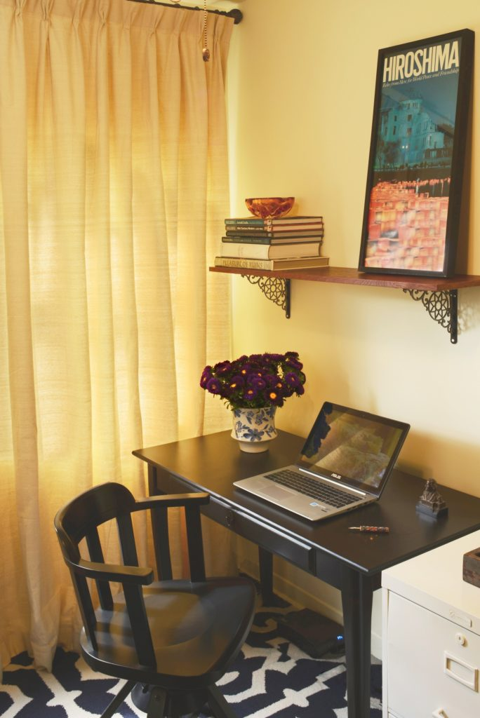 A teeny tiny Ikea desk in a home office with patterened rug and drapes made of drop cloth