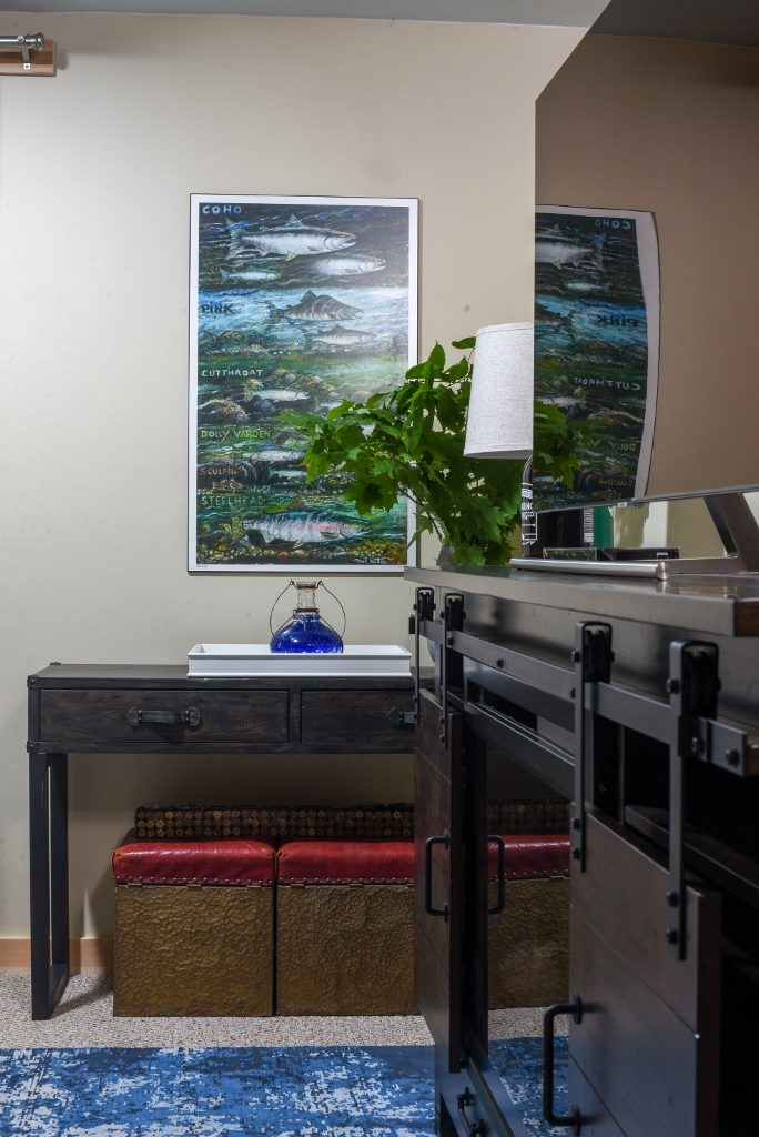 cottage family toom withw ide screen televesion, electric fireplace, vintage stools and an art poster in blues and green.