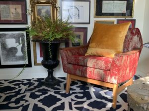 Mid century modern occassional chair in home office with art and family photo wall, ferns in planters