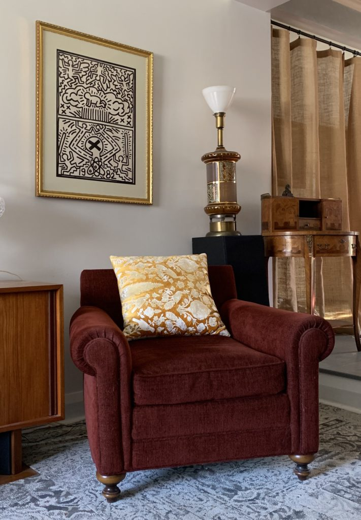 Gold graphic pillow on red chair in mid century home with vintage lamp and table, Keith Haring art and burlap drapes.