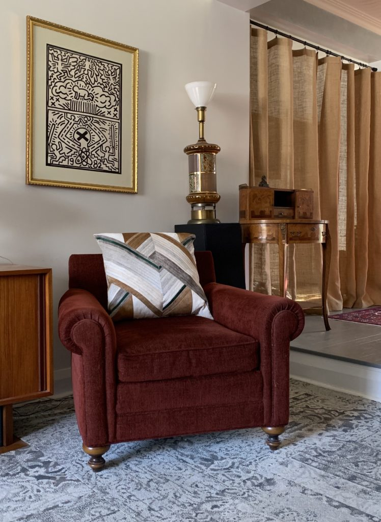Graphic hide pillow in grets and browns in traditional red chair with antique lamp and table, vintage art and burlap drapes.