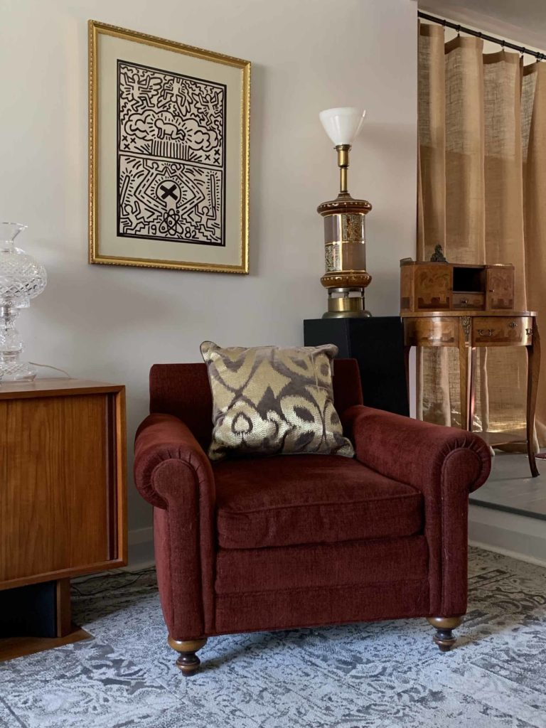 A gold and brown billow on a red chair with an antique lamp anf Keith Haring print in a gold frame.
