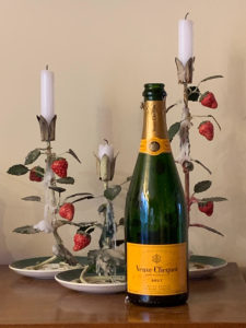 Champage bottle with vintage candle holders and candles in a cottage setting.